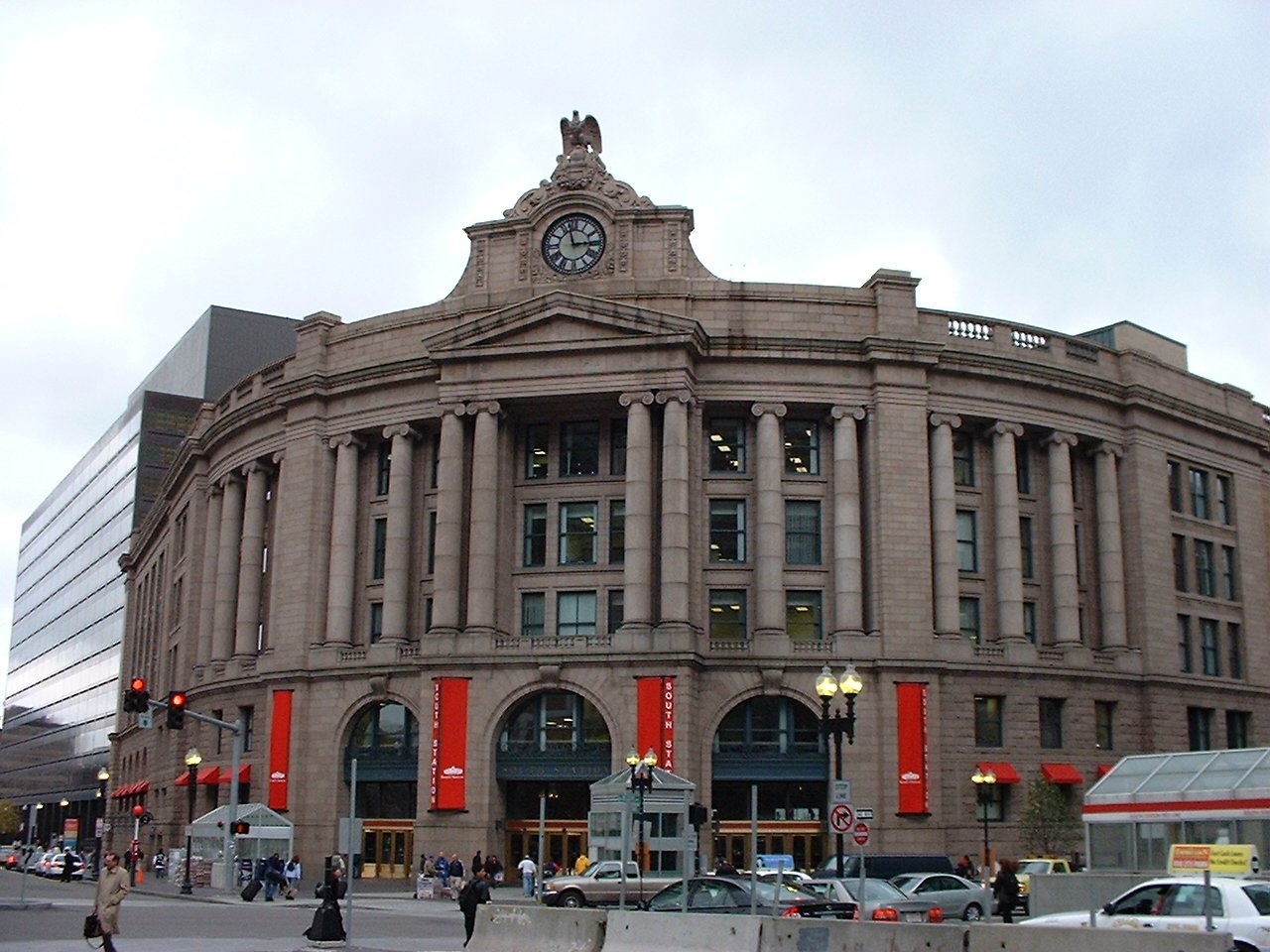 Photo of the front of South Station in Boston, MA. South Station — officially The Governor Michael S. Dukakis Transportation Center at South Station — is the largest railroad station and intercity bus terminal in Greater Boston and New England's second-largest transportation center after Logan International Airport.[4] Located at the intersection of Atlantic Avenue and Summer Street in Dewey Square, Boston, Massachusetts, the historic station building was constructed in 1899 to replace the downtown terminals of several railroads. Today, it serves as a major intermodal domestic transportation hub, with service to the Greater Boston region and the Midwestern and Northeastern United States. It is used by thousands of commuter rail and intercity rail passengers daily. Connections to the rapid transit Red Line and Silver Line are made through the adjacent subway station.