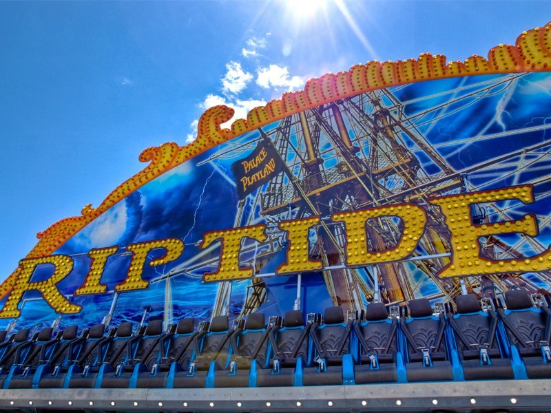 A photo of the Riptide, a thrill ride at the Palace Playland Amusement Park in Old Orchard Beach Maine. Riders are seated in a long row of seats facing out towards the midway. The ride will swing in constant motion to the right, and then later in the duration of the ride it will swing to the left, while the riders experience the sensation of centrifugal force.