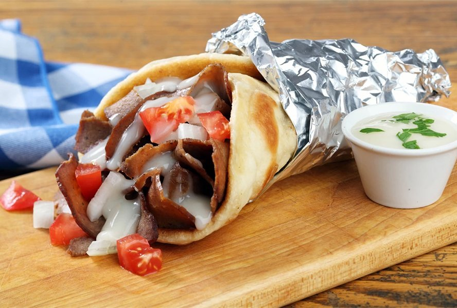 "A photo of a delicious Halifax donair. The Halifax donair was first invented in the 1970s by Peter Gamoulakos. Originally from Greece, he started selling Greek gyros (a pita stuffed with grilled lamb and tzatziki) from his restaurant located off the Bedford Highway. But the sandwich just didn't jive with the East Coast's ""meat and potatoes"" palate.  Swapping lamb for beef, the brothers whipped up a sweet ""donair sauce"" and tried again. This time, however, a feeding frenzy erupted and Halifax's signature dish was born. The late-night favourite has become so popular that in 2015, Halifax city council voted to make it the city's official food."